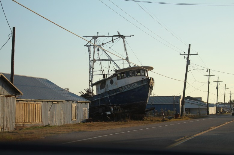 Massive fishing boat parked in the yard. (they can launch it from here into a canal that connects with the Gulf)
