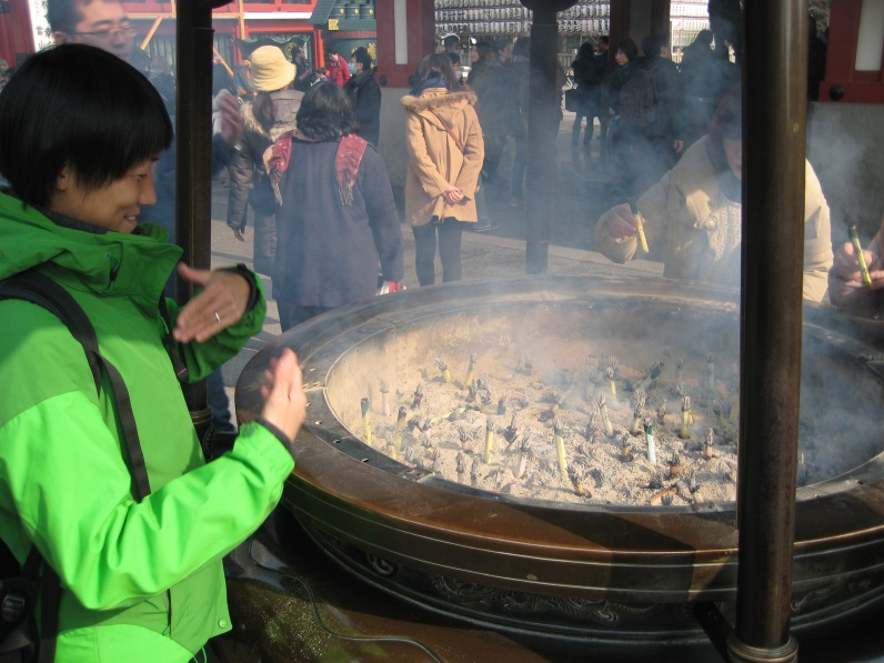 Burning Incense at the Temple. You are supposed to wave the smoke over your body.