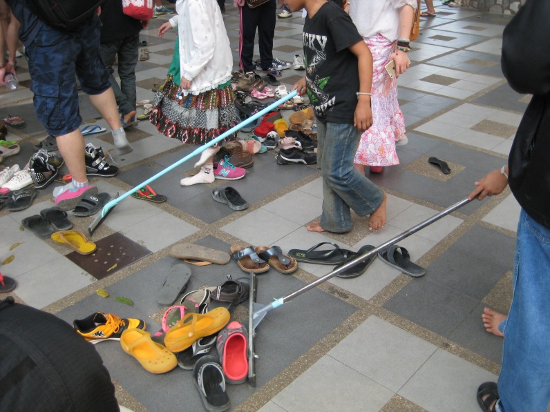 Shoes off to enter the temples, and kids sweep them into piles. Makes it really easy to find your shoes after