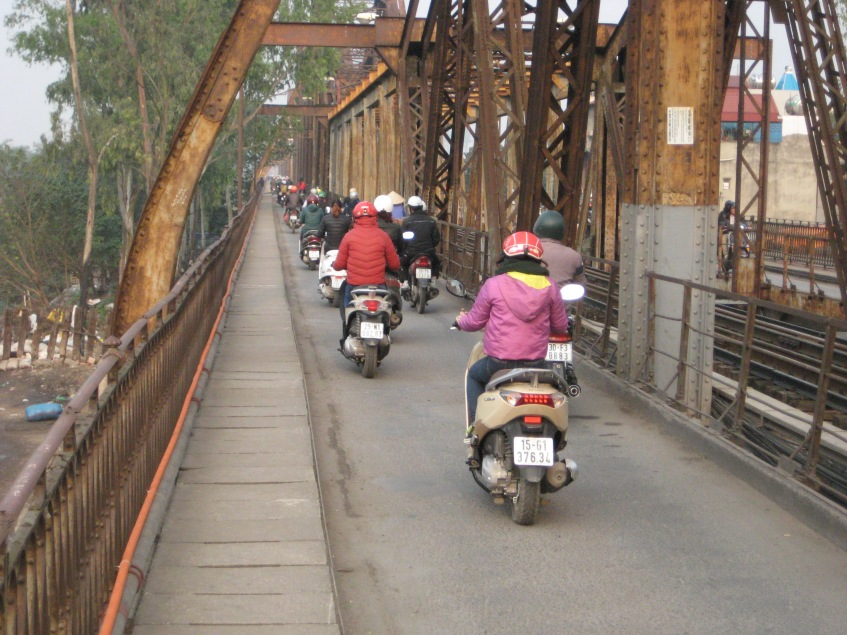Scooters and pedestrians are the only allowed users on this bridge. A train also runs in the middle.