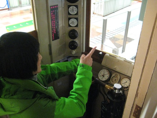 Aya driving a stationary train. This train is operational, except the wheels have been removed and placed in front of the car.