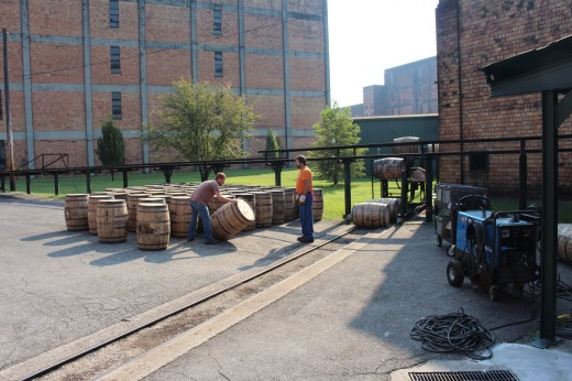Loading empting used barrels onto a truck, down the rails